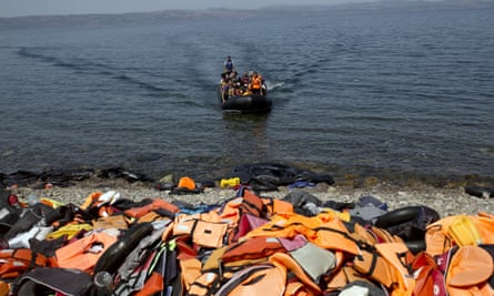 life jackets on beach and dingy in sea