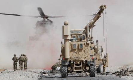 US troops assess the damage to an armored vehicle of Nato-led military coalition after a suicide attack in Kandahar province, Afghanistan.