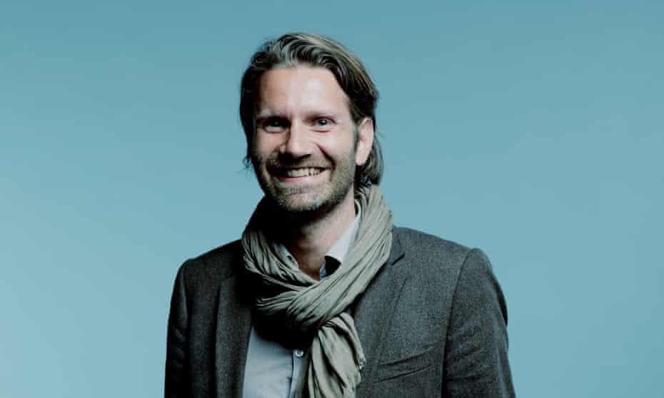 Meik Wiking in a jacket and scarf, smiling