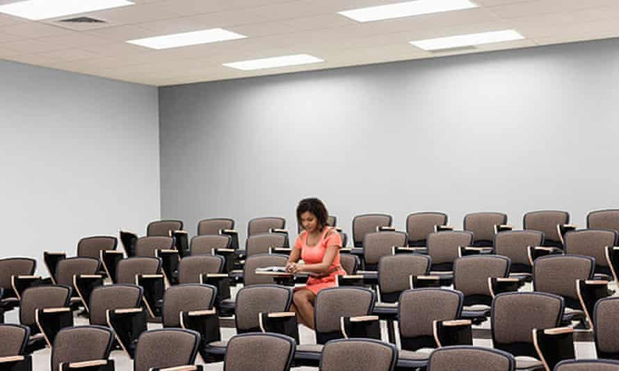 A university student sits alone in an empty lecture hall.