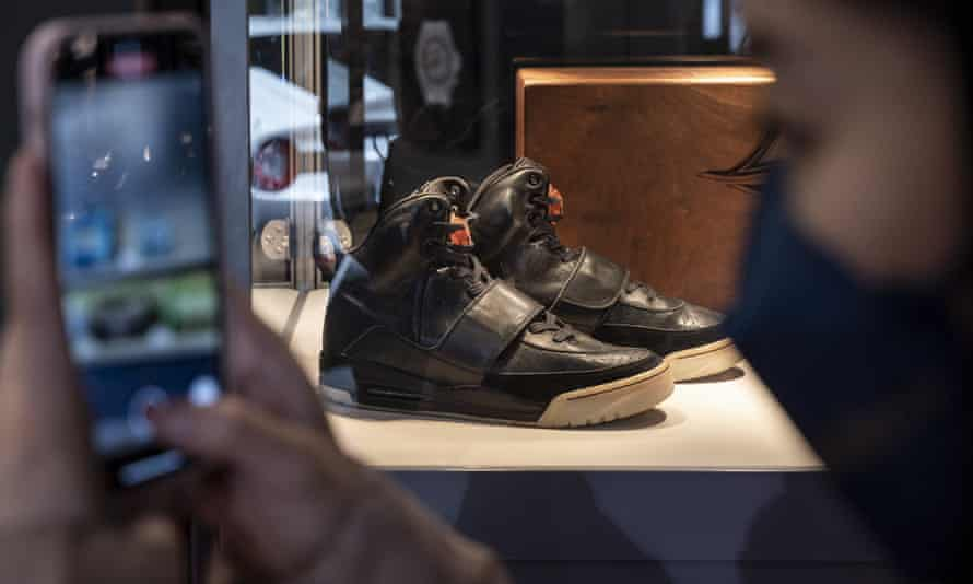 A visitor takes a picture next to Kanye West's Air Yeezy sneakers at an exhibition in Hong Kong on 16 April.