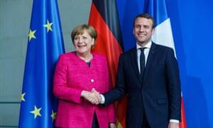 Angela Merkel greets Emmanuel Macron in Berlin.