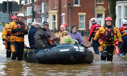 Residents are evacuated from their flooded homes in Carlisle on Monday after Storm Desmond brought severe disruption to areas of the UK
