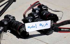 """Photojournalists leave their cameras on the ground with a note reading """"Freedom of Press"""" in Arabic during a protest outside the United Nations office in the occupied West Bank city of Ramallah"""