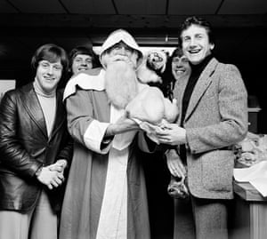 Santa Claus presents the Derby County players, including Roy McFarland, right, with their 1976 Christmas turkeys