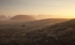 Sunset over the burial mounds, shrouded by mist, at Sutton Hoo. Suffolk, UK.