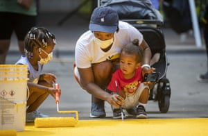 Kimberly McCarver helps her children Peyton and Dillion McCray paint Black Austin Matters on Congress Avenue.