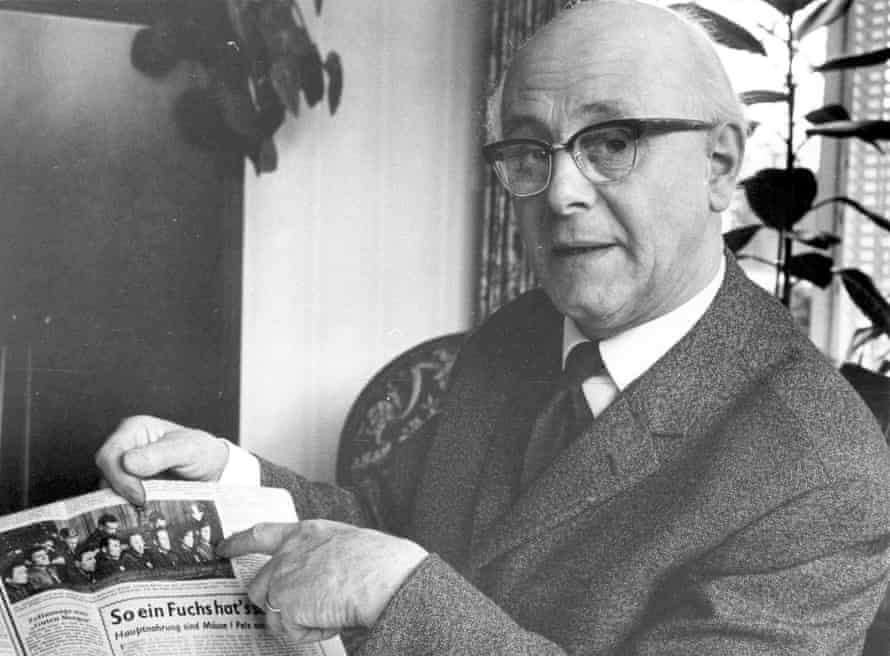 Hamelmann with a newspaper article showing the suspects in the dock in 1946. He is pointing to Czeslaw Godlewski whose release from jail he secured in 1969.