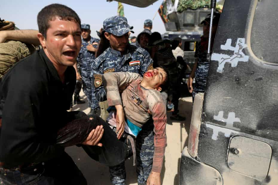 Iraqi federal police and a man carry a civilian injured while opening a booby-trapped shop in Tayaran district, western Mosul, on 12 March.