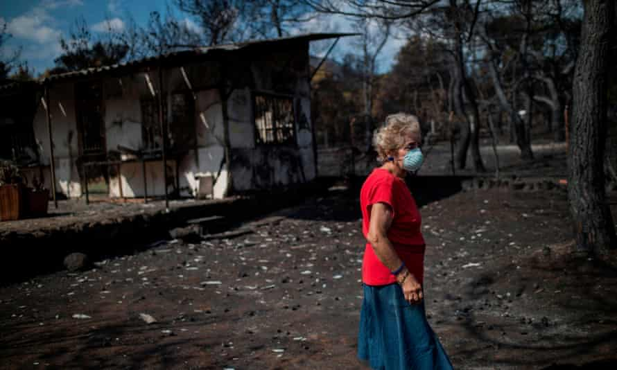 A woman wearing a mask walks in front of her burnt house near Athens