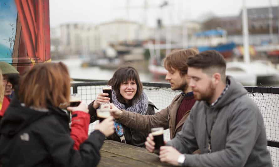 Young people clink glasses of Guinness on the Grain Barge, Bristol
