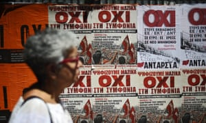 A woman passes a wall covered with Vote NO campaign posters on Greece's bailout referendum.
