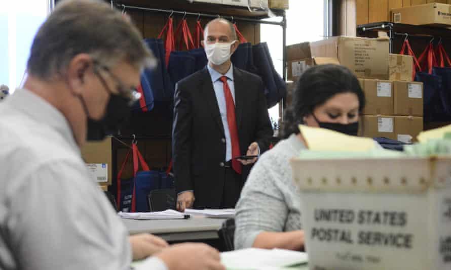 Douglas Bucklin, a Republican poll watcher, observes election bureau members opening provisional ballots in Pottsville, Pennsylvania.