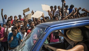 A woman takes a picture from her car of a group of Pakistani refugees protesting at their lack of progress obtaining transit papers in Kos.