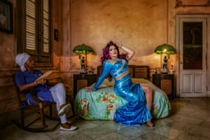 Drag queen Salma poses on the bed in a room in Havana, Cuba, 2019