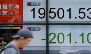 A man walks past a stock quotation board flashing the Nikkei 225 in Tokyo.