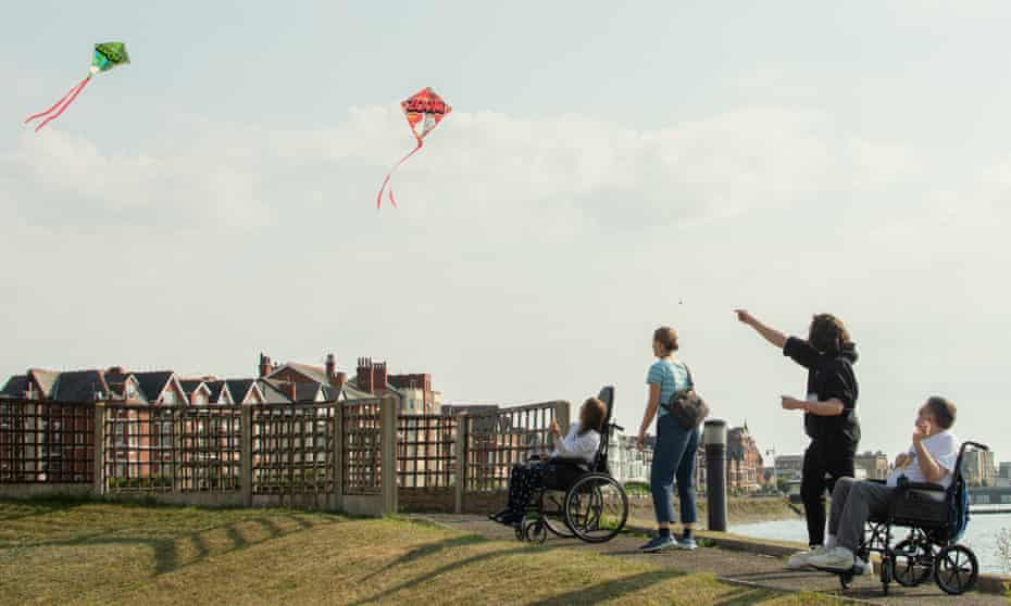 Two people in wheel chairs either side of two people standing. They are flying two kites and on a path near water