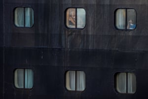 Passengers look from the windows of Holland America's cruise ship Rotterdam as it docks in Fort Lauderdale, US