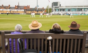 Supporters watch from a bench on the opening day of the county cricket season at Wantage Road, where Northamptonshire played Glamorgan.