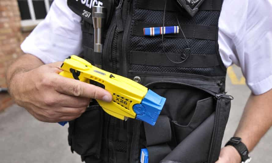 A male police officer with a drawn stun gun