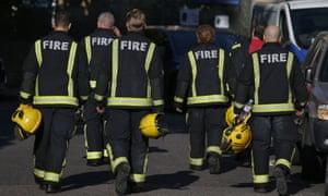 Members of the fire brigade walk near Grenfell Tower