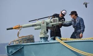 Crew members of a whaling ship check a whaling gun or harpoon before departure at Ayukawa port in Ishinomaki city.