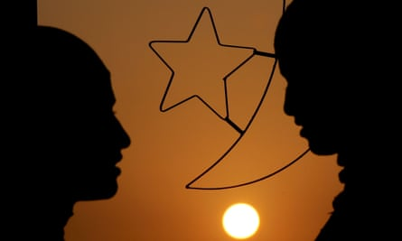 Women stand in front of a window decoration of Islam's crescent moon and a star