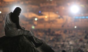 """A pilgrim prays on a rocky hill called the """"Mountain of Mercy,"""" on the Plain of Arafat, near the holy city of Mecca."""