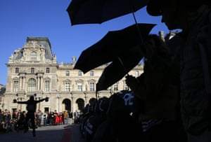 A protest outside the Louvre pyramid, calls on the museum to cancel its contracts with French oil giant Total and Italian oil company Eni