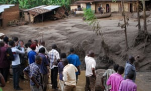 Survivors look on as flood waters pass through homes in a village in Uganda's Bududa district