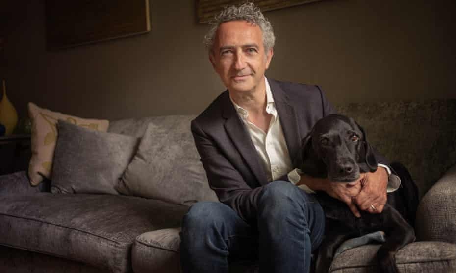 Writer Simon Garfield and his dog Ludo sitting on the sofa in their home