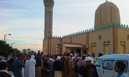 People gather at the site of the Sinai mosque where a bomb and gun assault left at least 235 people dead and scores more injured.