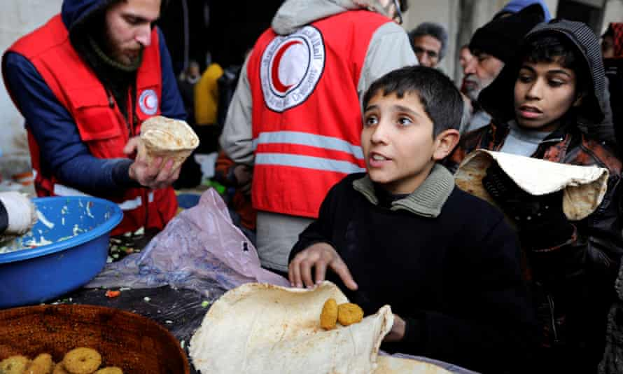 Syrians evacuated from eastern Aleppo, get food aid from the Syrian Red Crescent inside a shelter in government controlled Jibreen area in Aleppo.