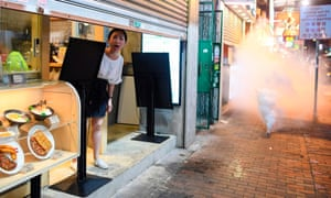 A woman looks out of her shop as police  fire tear gas shells to disperse pro-democracy protestors in the Sham Shui Po area, Hong Kong, China