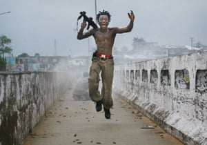 Monrovia, 2003A Liberian militia commander loyal to the government, exults after firing a rocket-propelled grenade at rebel forces at a key strategic bridge July 20, 2003