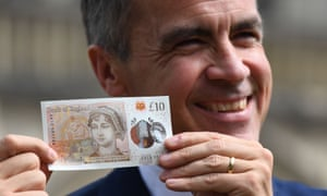 Bank of England Governor Mark Carney poses with one of the central bank's new ten pound notes, featuring author Jane Austen