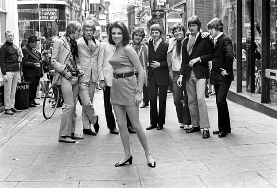 A woman in a mini-skirt attracts male attention on Carnaby Street, London, in the 1960s.