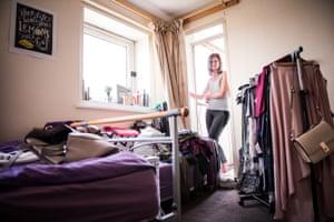A woman stands in the doorway of her bedroom