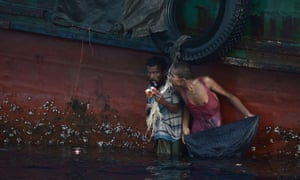 A Rohingya migrant eats food dropped by a Thai army helicopter after he jumped to collect the supplies at sea from a boat drifting in Thai waters off the southern island of Koh Lipe in the Andaman sea.
