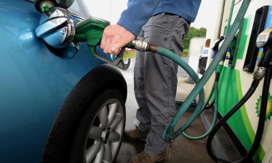A man fills his car with petrol at the pumps