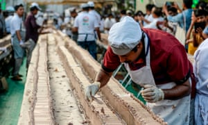 A baker puts the finishing touches on a cake in India in an attempt aim to break the Guinness World Record for the longest cake.