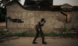 A member of the DRC armed forces walks past a burnt building in the city of Yumbi