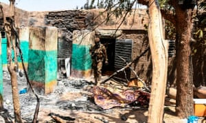 A soldier walking among rubble of a house destroyed during an attack on the village of Ogossagou, near Mopti, where over 130 Fulani villagers, including women and children, were killed.