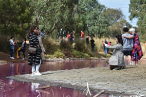 Visitors at the saltwater lake in Westgate Park, where the water has turned pink due to high levels of salt and algae and has become a popular tourist destination in Melbourne, Australia