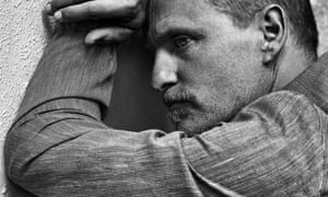 Woody Harrelson leaning against a tree
