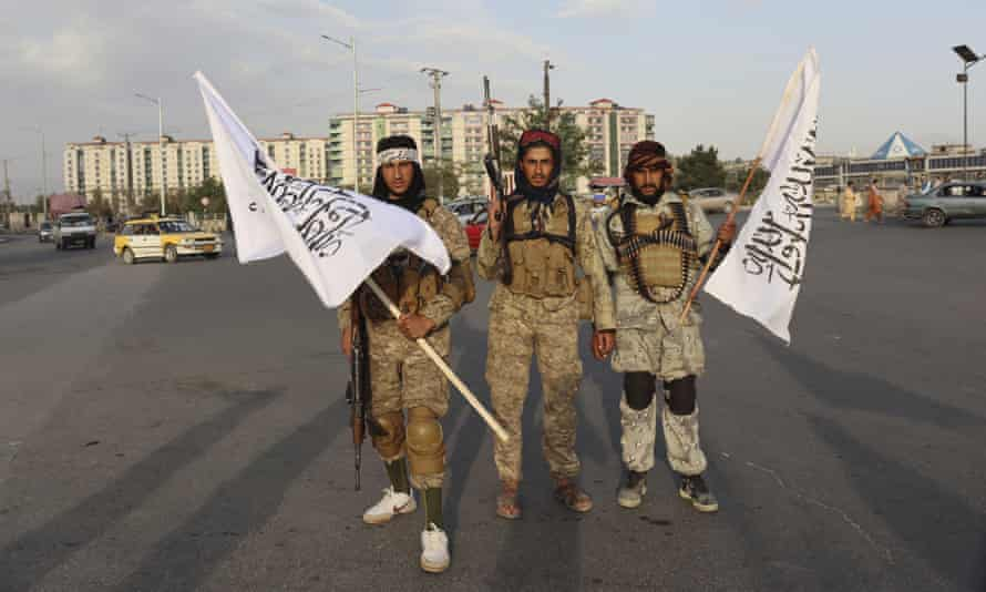 Taliban fighters hold flags in Kabul