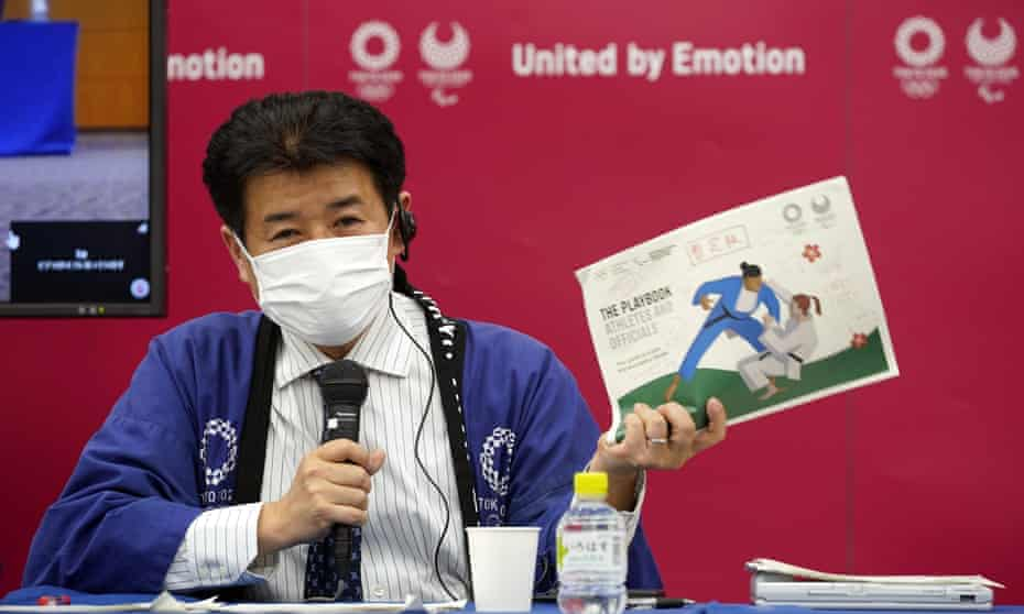 A Tokyo 2020 official holds a sample of the Covid-19 playbook of during a press briefing