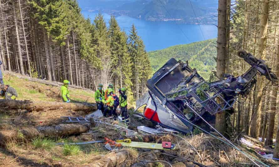 Rescuers work by the wreckage of a cable car after the crash near the summit of the  Monte  Mottarone line in northern Italy, on 23 May.