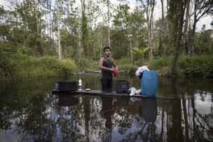 A young man washes his clothes in a pond in the viallge Ka 'a kyr, in Para state, Brazil. Villages along the Guama and Gurupi rivers that divide the Alto Rio Guama Indigenous Reserve can range in size from a few dozen people to hundreds