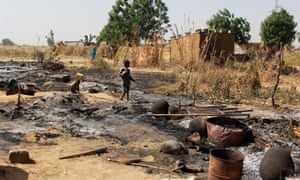 A boy walks past the remains of a village burnt down by Boko Haram on the outskirts of Maiduguri.